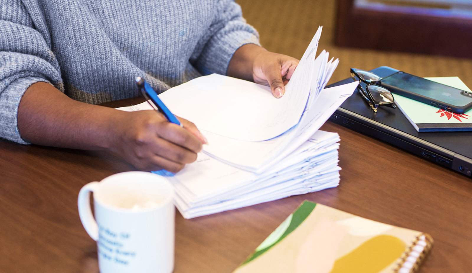Woman writing on stack of paper